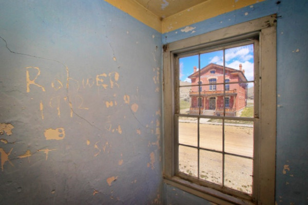Bannack's former court house and Hotel Meade are pictured through the window of another structure across the street.