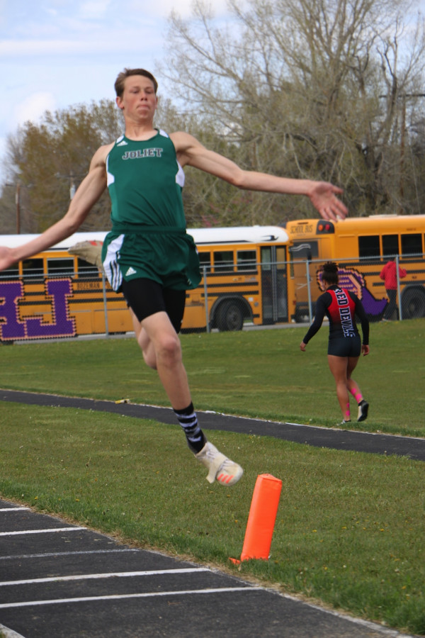 Joliet's Ty Olson leaps in the air during the long jump competition.