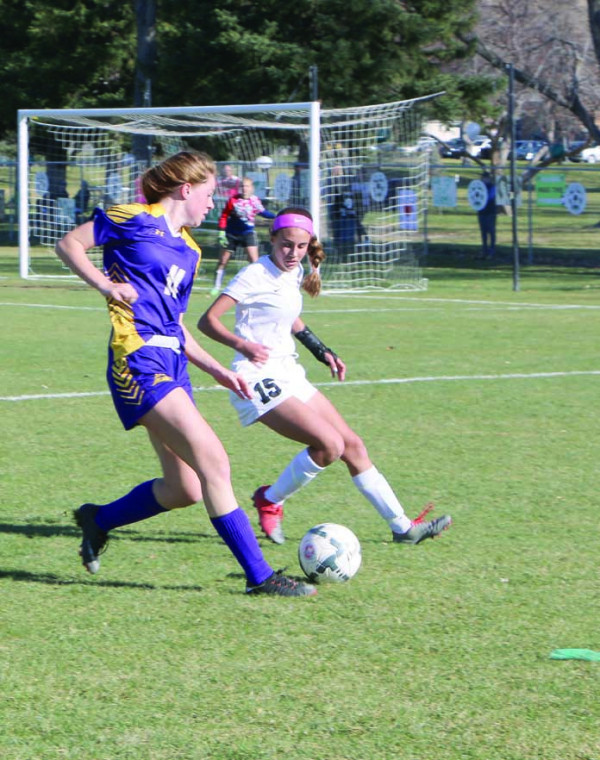 Photo by LHS managers. Morgan Maack tries to get past a Central defender in the first half of the championship game.