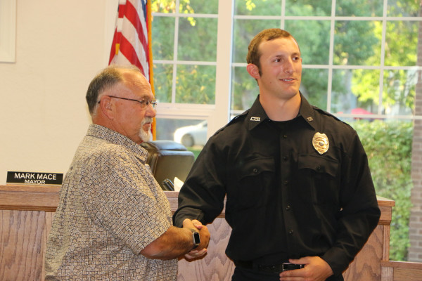 Outlook photo by Kathleen Gilluly.  Newly sworn in Laurel Police Officer Chase Rasmussen is congratulated by Mayor Mark Mace after receiving his badge at the Laurel City Council meeting Tuesday evening. Officer Rasmussen is from Helena, but is excited to be in Laurel. The 25-year-old worked hard to become a police officer and is eager to begin training. His parents, Roy and Gina Rasmussen, girlfriend Annie and her brother, a Montana Highway Patrol trooper were at the meeting to witness the ceremony.