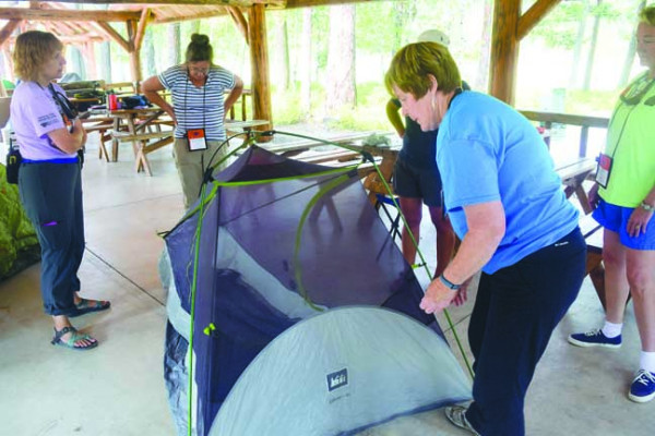 BOW Coordinator Liz Lodman, left, and participants Patti Beckley, of Missoula, center, and Kathy Milodragovich, of Butte, right, learn how to set up a lightweight tent under the picnic pavilion at the Lubrecht Forest, Aug. 5.