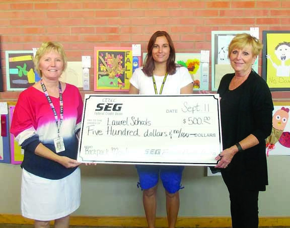 President of SEG Federal Credit Union Janice Lehman delivered a $500 check for the Laurel Elementary Schools Backpack Meal Program. On the left, West School Principal Kelly Anderson  and Counselor Danielle Smith accept the donation. Meal packs are assembled and distributed to approximately 60 chronically hungry students from kindergarten through eighth grade. Each pack costs $4 and is given to kids to help them get through the weekends.