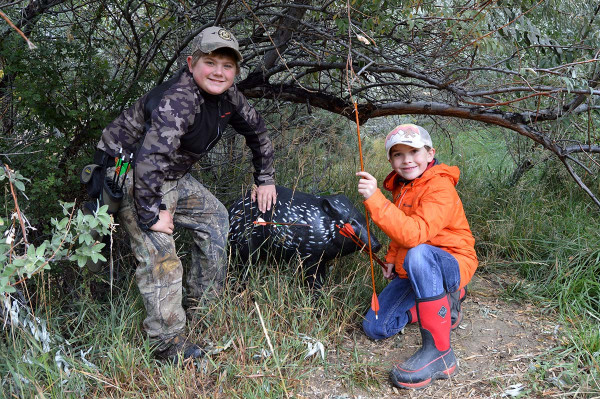 Gavin Thompson and Riley Tedeschi check out an arrow in a 3D target of a wild pig.