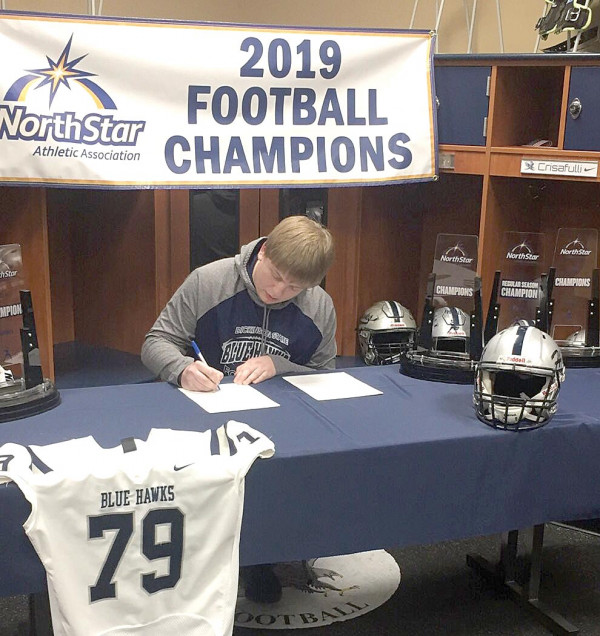 Austin Dennis of Park City signs his football contract for the DSU Blue Hawks.