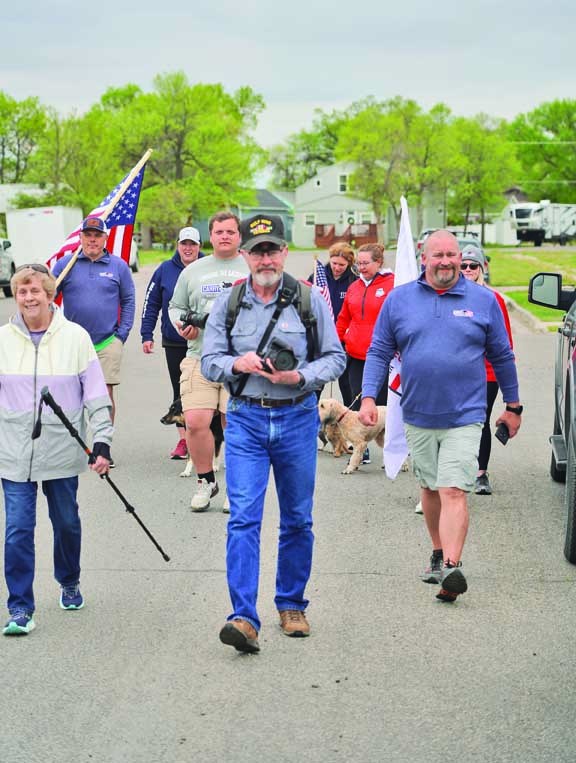 Ed and Charlene Saunders (middle and left) lead the way for the Carry the Load walk to the Yellowstone National Cemetery last Thursday. The Dallas–based non–profit travels the country in a bus to honor fallen veterans around Memorial Day. Outlook photos by Chris McConnell
