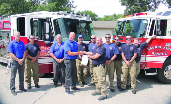 "In August, CHS fire and safety personnel present a $50,000 donation check to the Laurel Volunteer Fire Department to purchase new ""jaws of life"" extrication tools."