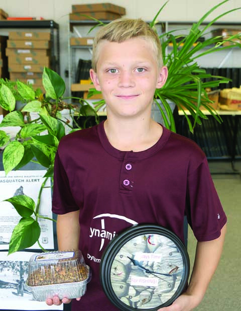 "Tayden Lanaghan, 10,  is in his 2nd year of participating in 4-H for the Laurel Road Runners. He is the son of Brittany Lanaghan and Travis Lanaghan. This year for the Montana Fair Tayden made a ""flock block,"" his own take on homemade chicken food. He also made a fishing clock and is participating in livestock competitions with a chicken, guinea pig and mouse. He is pictured with his fishing clock and ""flock block."""