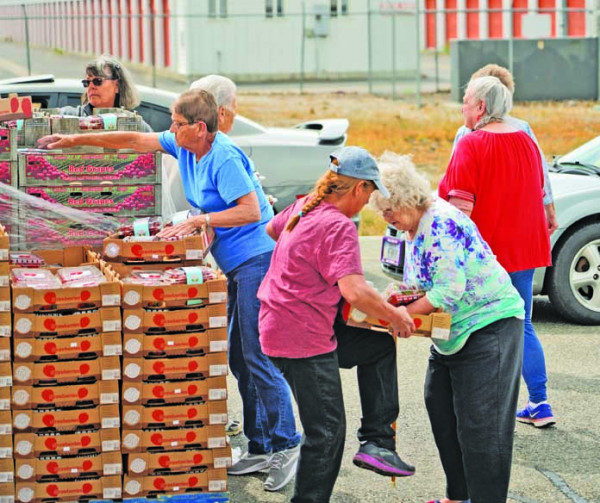 Staff of Laurel Community Hope help residents carry their food boxes to their cars on Milwaukee Rd. Families received food boxes from Grasmick Produce out of Idaho as part of COVID–19 relief efforts.