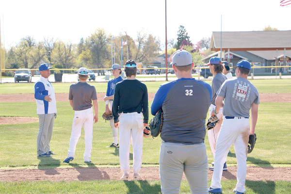 A group of young athletes who are on their second day of tryouts for the Laurel Dodgers stand a safe distance from each other while taking instructions from one of the team's assistant coaches.