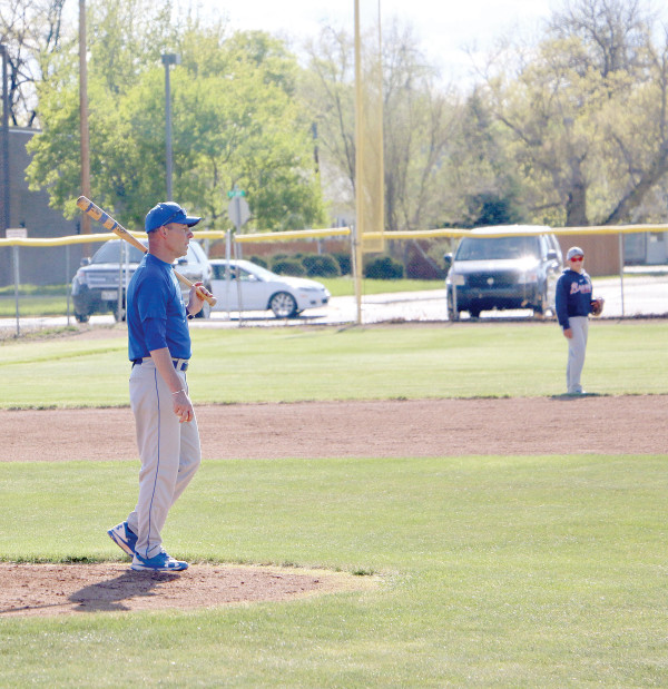 Head coach for the Dodgers, Doug Studiner, takes a break from hitting fly balls to direct players in the outfield.