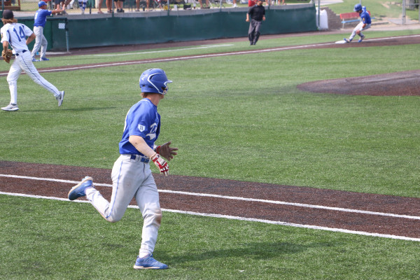 Keagan Thompson runs down the first baseline eyeing a teammate rounding third; in the distance Coach Studiner motions the player to stop at the base.
