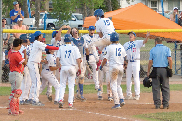 Richie Cortese (#15) celebrates with his Dodger teammates as he crosses the plate after a 3rd inning homer during a 9–6 win over the Lewistown Redbirds last Thursday.