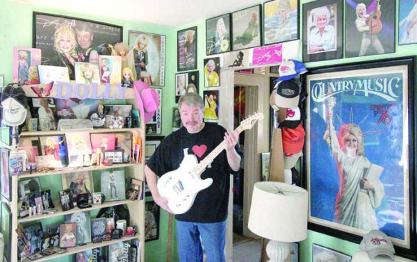 "Laurel resident Wes Salveson is a Dolly Parton ""superfan"" who has been collecting memorabilia for more than 40 years. He is shown in one section of his home holding one of his prized possessions, an electric guitar autographed by Parton."