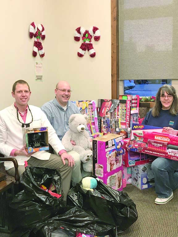Shown from the left are the friendly dentists at Laurel Family Dental Dr. Jordan Dobmeier and  Dr. Sam Pollock. With them is Lisa Foreman, Community Hope's director and a number of donated toys from the practice's third annual toy drive. By partnering with Community Hope the dental clinic is able to collect toys for Laurel area children for the holidays. This year's toy drive was a great success that will benefit many children.