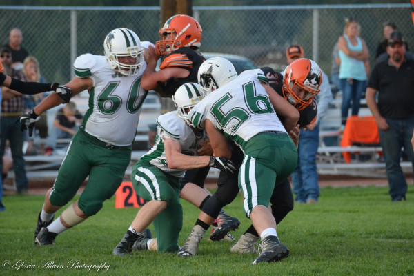 Photo courtesy Gloria Allwin. Kirby Caiden (#60), Justin Harris (#30) and Grant O'Rourke (#56) wrap up a Huskies runner during their commanding 48-16 win over Absarokee on Friday. The J-Hawks had a strong defensive showing, allowing zero points in the first half.