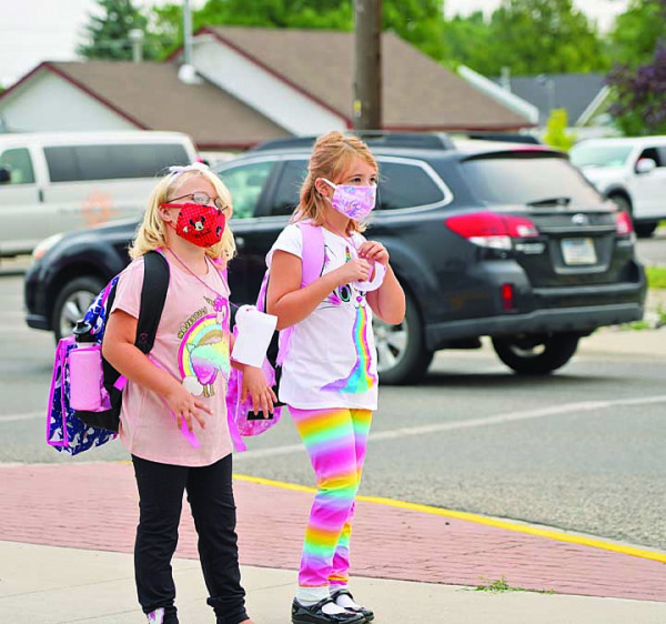 Two students wait their turn to enter West School on the first day of class.