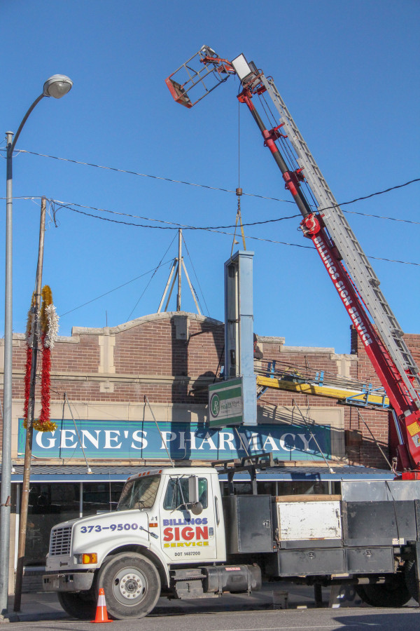 Billings Sign Company employees use a crane to remove the Gene's Pharmacy marquee on Tuesday afternoon to make room for a new business going into the building.