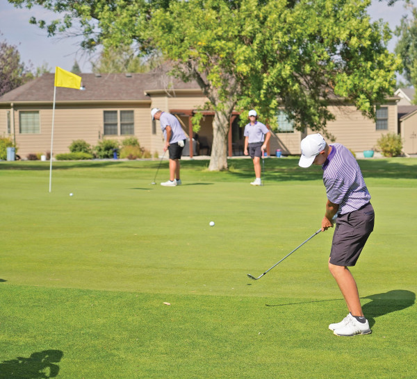 Carson Hackmann chips to the 17th hole at Lake Hills en route to shooting 73 and winning his first Eastern A Divisional title on Sept. 24. The team finished second behind Billings Central. Outlook photo by Chris McConnell