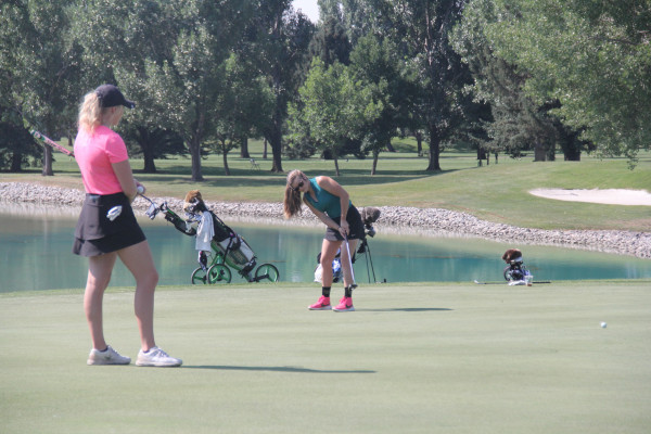 Photo by Chris McConnell.  Park City native and new Rocky Mountain Assistant Golf Coach Kyla Clancy gets a feel for the greens during the Montana Women's State Amateur practice round on Wednesday at Laurel Golf Club while RMC sophomore golfer Hayden Flohr watches.