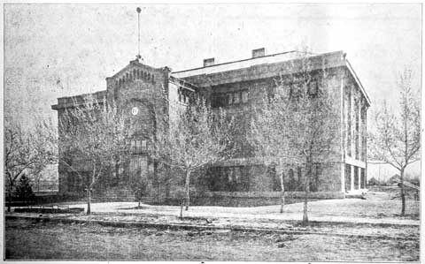 The gymnasium still stands behind the Administration Building (known as the old middle school). In 1920, as depicted, the building hadn't yet been transformed into a WWII fall-out shelter with the addition of the outer brick wall. The building is no longer in use.