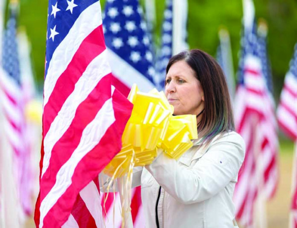 Krista Whitfield puts yellow ribbons on one of the 1,000 American flags on display during the Laurel Exchange Club's Healing Field event.