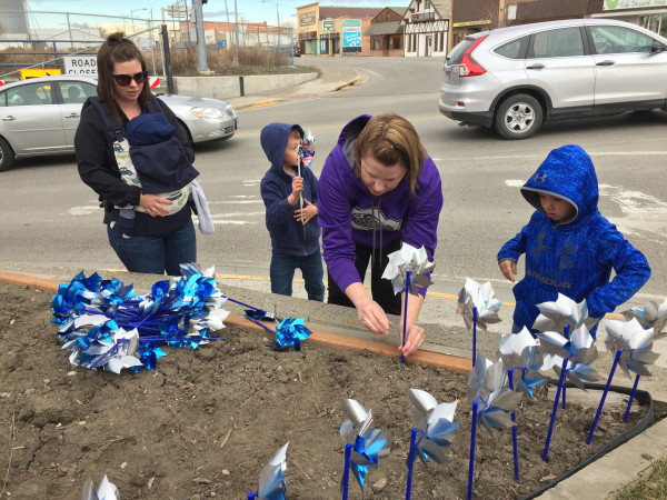 Exchange Club Member Misty Wittman and her son are seen planting the Blue Pinhweels for Child Abuse Prevention Month.
