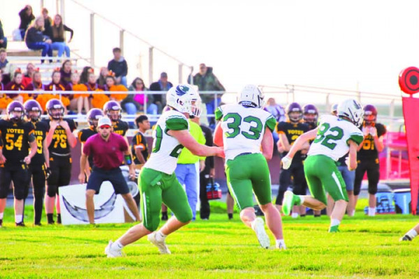 Hayden Ward hands off the ball to Rye Brastrup (#33) during Joliet's opening season win against Shelby on Saturday. The J–Hawks came back in the game to beat the Coyotes 36–20. Photo courtesy Michelle Carpenter