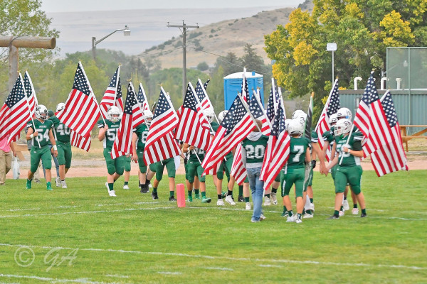 The Joliet football team runs on the field carrying American flags before their Homecoming matchup against Twin Bridges. Photo courtesy Gloria Allwin