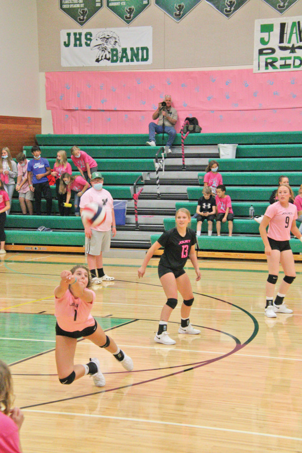"""Makenna Bushman goes for the dig while Kylia Kliner (13) and Kyelynn Coombe (9) watch during Joliet's """"Pack It Pink"""" night. The J–Hawk volleyball team ended up playing each other after their scheduled opponent, Columbus, got sent home due to the coronavirus. Photo courtesy Michelle Carpenter"""