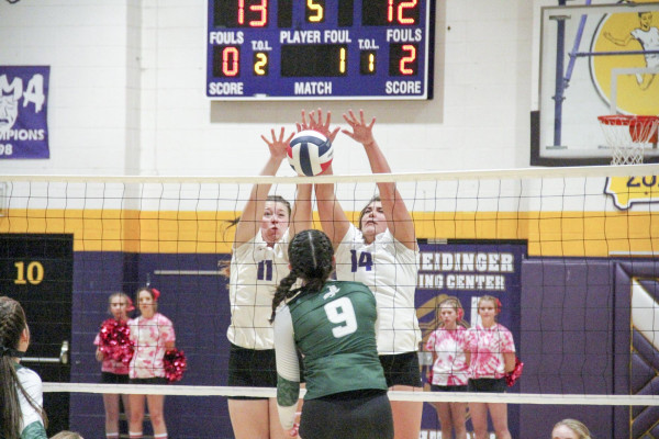 Riley Chapman (left) and Saige Weimer block the ball against Joliet in Tuesday's home match. The J-Hawks downed the Locos in three games 25-15, 25-15 and 25-19. Chapman led Laurel in blocks with four and Weimer led in kills with five.