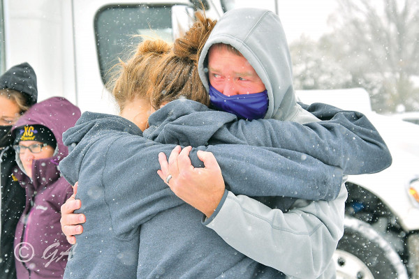 Laurel Cross Country Coach James Haskins has an emotional celebration with members of the Lady Locos team after they completed a perfect season and won the Class A State Championship in Kalispell.