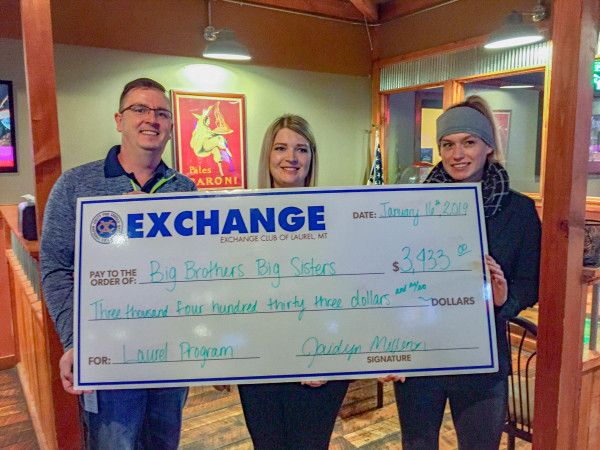 Justin Whitfield and Jaidyn Milliron present a check of $3,433 to a member of the Big Brothers Big Sisters of Yellowstone County. The Laurel Exchange Club gave away nearly $7,500 to worthy causes Jan. 16. Much of the money was raised through the Healing Field.