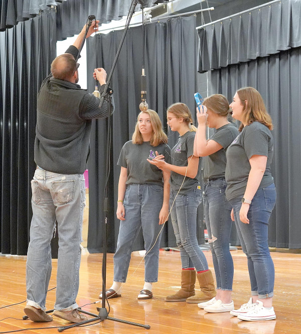 Outlook photo by Chris McConnell                        Four members of the LHS choir prepare to sing harmony on the recording of a local musician's upcoming video on Tuesday in the high school auditorium. From the left are sound engineer Wes Urbaniak, Megan Maida, Taylor Noble, Maren Pollock and Ashley Goss.