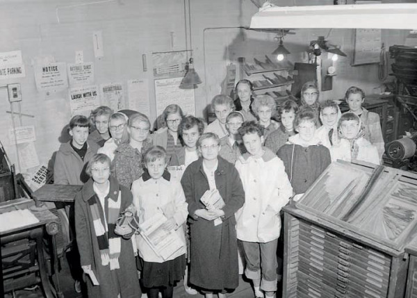 Can you help identify this photo by Lowell's Fotos? It appears to be a visit to the Laurel Outlook office. Two of the signs on the back wall show the year as 1952. The Farmers Union Central calendar does not depict 1952. Call the Laurel Outlook 406-628-4412 (Mon.-Thurs. 9-5) or email jobs@laureloutlook.com.