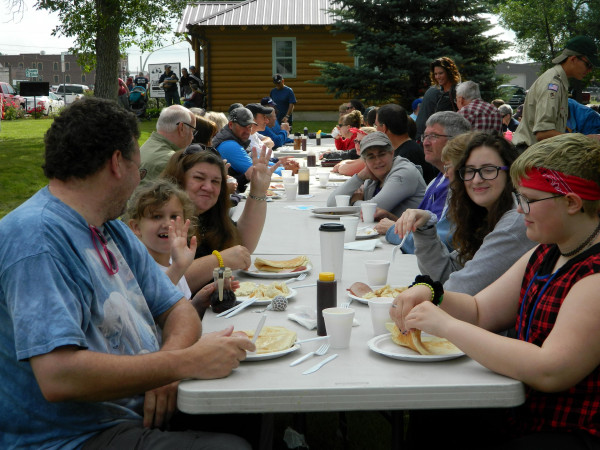 A full table of diners enjoys breakfast served by the Jaycees and other volunteers at Firemen's Park beginning at 6 a.m. on the Fourth of July. There were a number of tables set up and they remained consistently full.                      Outlook photo by Kathleen           GIlluly