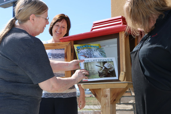 Pictured from the left, Peggy Leggett, Amy Sullivan and Denise Paffrath fill the Little Free Library book box, located next to the Pizza Hut restaurant in Laurel.