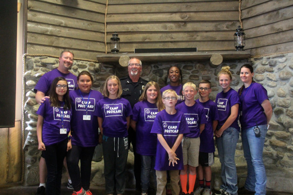 """Proving there's no """"I"""" in team, Laurel's Camp Postcard team members from the left are School Resource Officer Kyle Bryant, Alanis Durant-Torres, Promise Loan Elk, Lucy Meling, Laurel Police Chief Rick Musson, Brooklyn Emineth, Kaleb Lawson, Braelyn Marshall (in back), Brandon Folts, Cooper Davis, Junior Mentor Megan Flemmer and Laurel reserve police officer Tammy Harpster."""