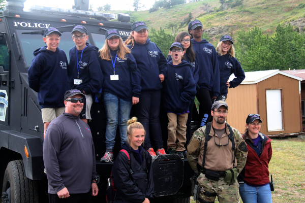 Laurel's Camp Postcard team members are seen on Yellowstone County's Tactical Respone Team vehicle. Back row from left: Brandon Folts, Cooper Davis, Brooklyn Emineth, Promise Loan Elk, Kaleb Lawson, Alanis Durant-Torres, Braelyn Marshall, Lucy Meling. Front row: Laurel School Resource Officer Kyle Bryant, Junior Mentor Megan Flemmer, Yellowstone Counter Undersheriff Kevin Evans, and Laurel reserve officer Tammy Harpster.