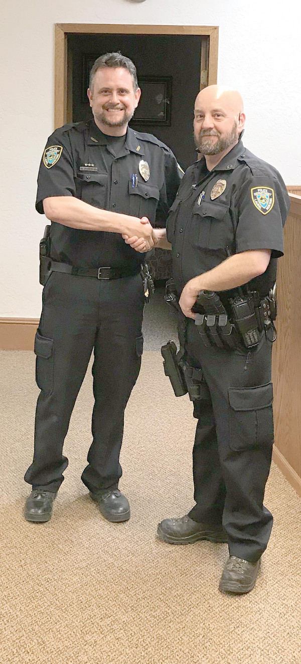 Laurel Police Chief Stan Langve (left) congratulates Travis Pitts who was promoted to LPD Captain at a City Council meeting.