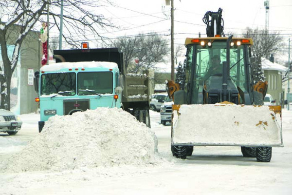 City employee Roy Voss scooped and dumped snow into a small dump truck last Thursday after a Wednesday night stormed dropped a few inches on Laurel. The city crews were working to move the snow before the big storm predicted for the weekend hit.