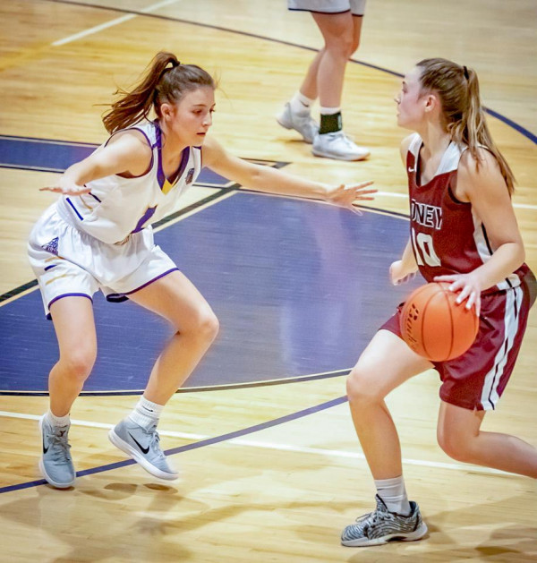Photo courtesy of Kathleen Linger                        Laurel senior Aspen Cotter (white) pictured here guarding a Sidney player with the ball. On Senior night, Aspen scored a team-high 13 points, including two three pointers, two rebounds, and three steals.