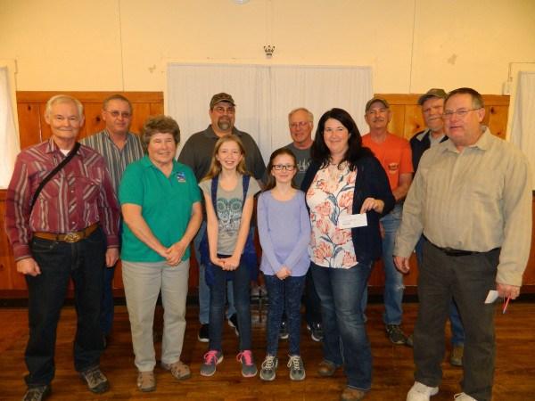 Shooters from the Yellowstone Rifle Club Juniors program are shown along with members of the Tri-County Sportsman handing out the checks. Among the Sportsman's group are Mike Connoly, Kent Miller, Jim Simons, Stu Korth and Curt Lord.