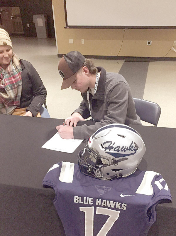 Photos taken from DSU Football (@BlueHawkFB) Twitter page                        Troy Fiscarelli of Park City signs his letter of intent with the Dickinson State University Blue Hawks.