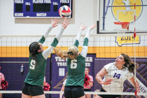 Outlook photo by Chris McConnell. Joliet's Vanessa Nowak, left, and Skyler Wright block a scoring attempt from Laurel's Saige Weimer in last week's match. The J-Hawks defeated the Locos in three games.
