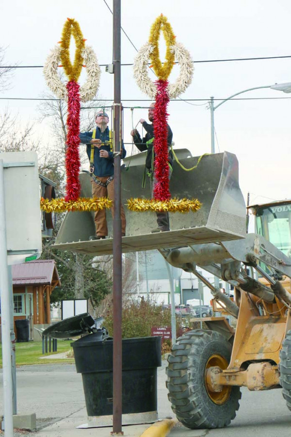 Among the volunteers helping members of the Laurel Chamber of Commerce with the yearly task of making Laurel merry are Tomas Sarkela and Koby Nielsen in the bucket loader and Rob Schessler operating it. Other crews carried the decorations to each location on a flatbed and got them ready to be hung.