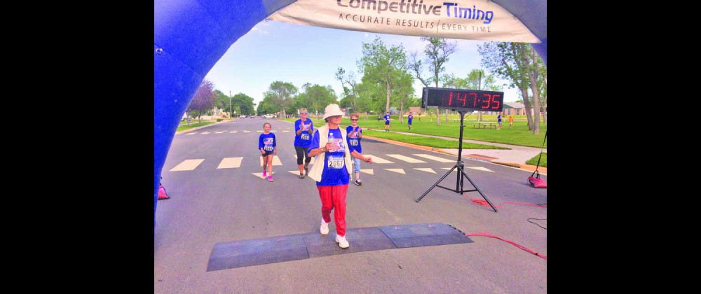 Edna Stepper, 74, receives encouragement from SOW Ministry volunteers as she crosses the finish line of the Chief Joseph Run on July 4 in Laurel.