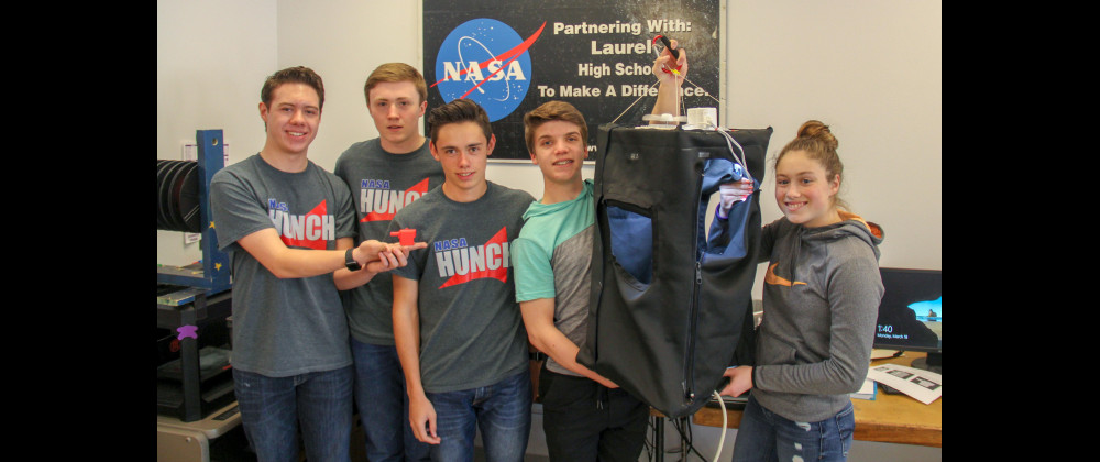 Outlook photo by Chris McConnell                        The two Laurel NASA–HUNCH teams whose projects made it to the Final Design and Prototyping review at NASA's Johnson Space Center are seen in their classroom this week. Connor Reidlinger and Draven Earls are seen on the left with their ARED Cable Hood and Ethan Gradwohl, Ethan Riedesel and Cassie Sampson are seen with their Collapsible Sleeping Quarters scale model. Not pictured is Daniel Adams.