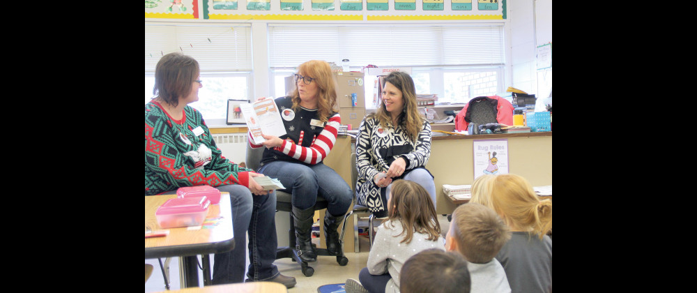 "Outlook photo by Chris McConnell                        First Interstate Bank volunteer Dawn Smith reads ""Chicken in Mittens"" to South School students on Dec. 7 while FIB's Dawn Carlson (left) and United Way of Yellowstone County's Literacy Coordinator Brenda Ludwig watch. After reading the books to students in each classroom, the students were presented with a copy of the book. FIB and UWYC have been providing free books to area students during the holiday season since 2007 and this year delivered nearly 9"