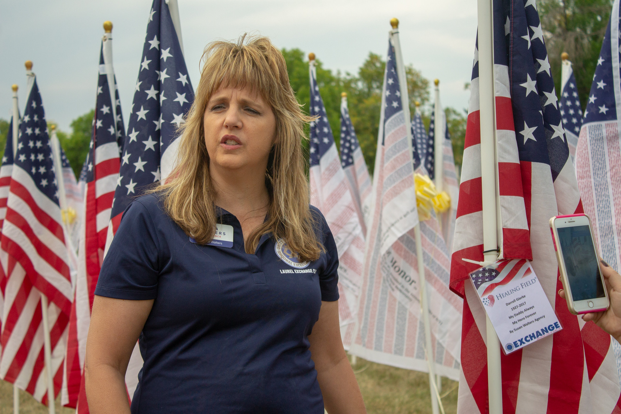 """Susan Walters dedicating the first flag to her father Darrell Gierke with the tag saying """"My Daddy Always, My Hero Forever, by Susan Waters Agency"""""""