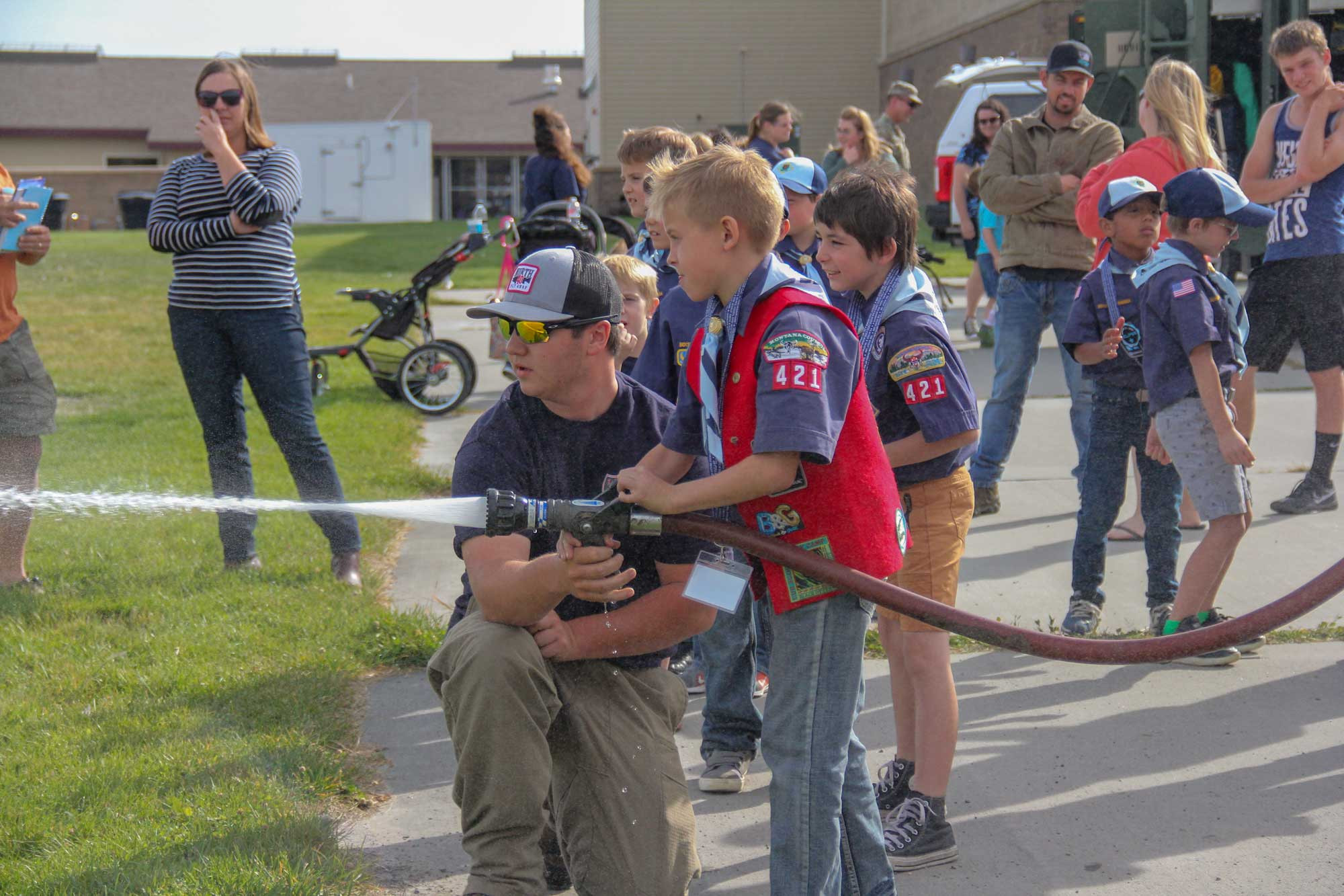 Laurel Volunteer Fire Department new hire Levi Jones helps a Laurel Cub Scout operatethe fire hose at the Middle School last week during Pack 421's fall meeting. A variety ofemergency personnel as well as the Billings Army Reserve and DNRC were on hand toshow the scouts a little of what they do.